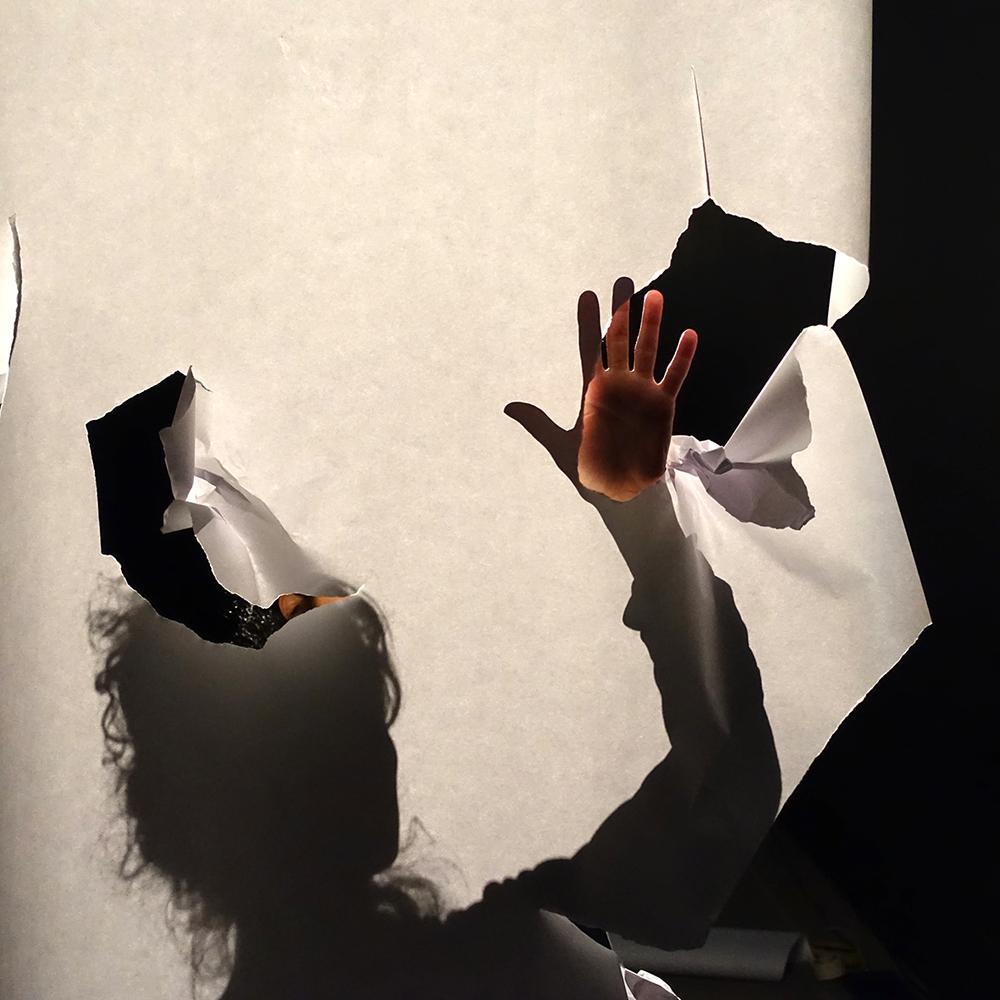 Josie Cáceres interacting with long stripes of paper with contact microphones at the Center for Contemporary Art, Quito -Ecuador, 2015.  Josie Cáceres interactuando con una de las tiras largas de papel con micrófonos de contactoen el Centro de Arte Contemporáneo de Quito, Ecuador 2015.  50 min. Dimensiones variables