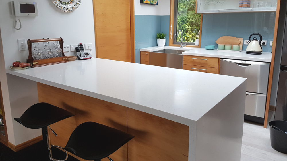 Back bench and large counter top with waterfall end in TriStone Antarctic Snow.