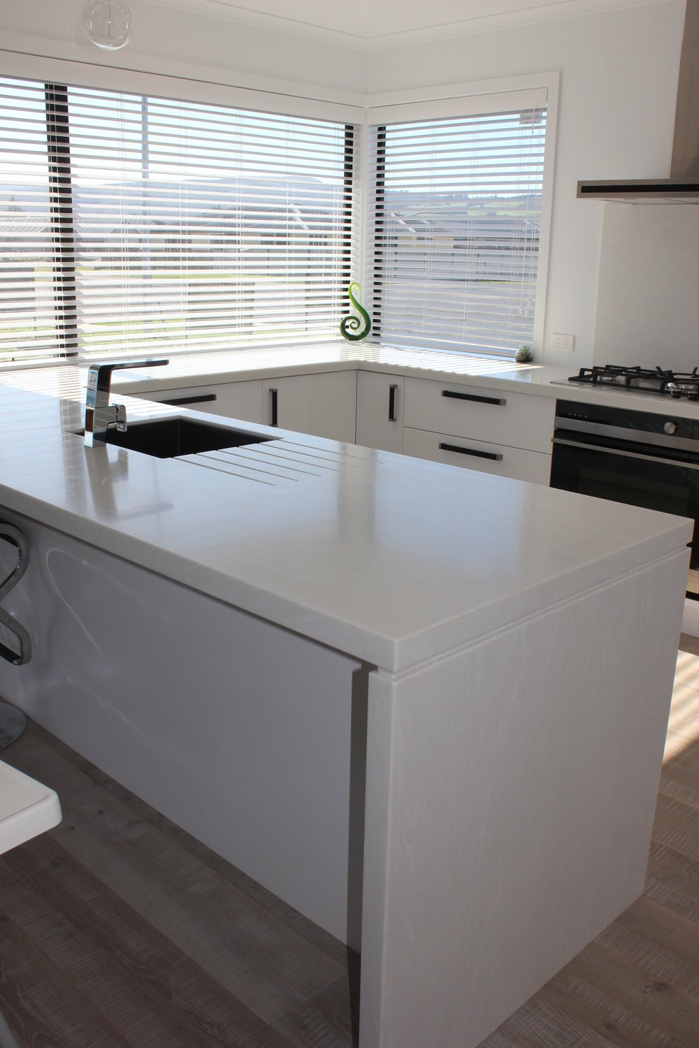 TriStone Milk Grotto benchtop (U-shaped) with negative detailed waterfall end and drainer grooves.