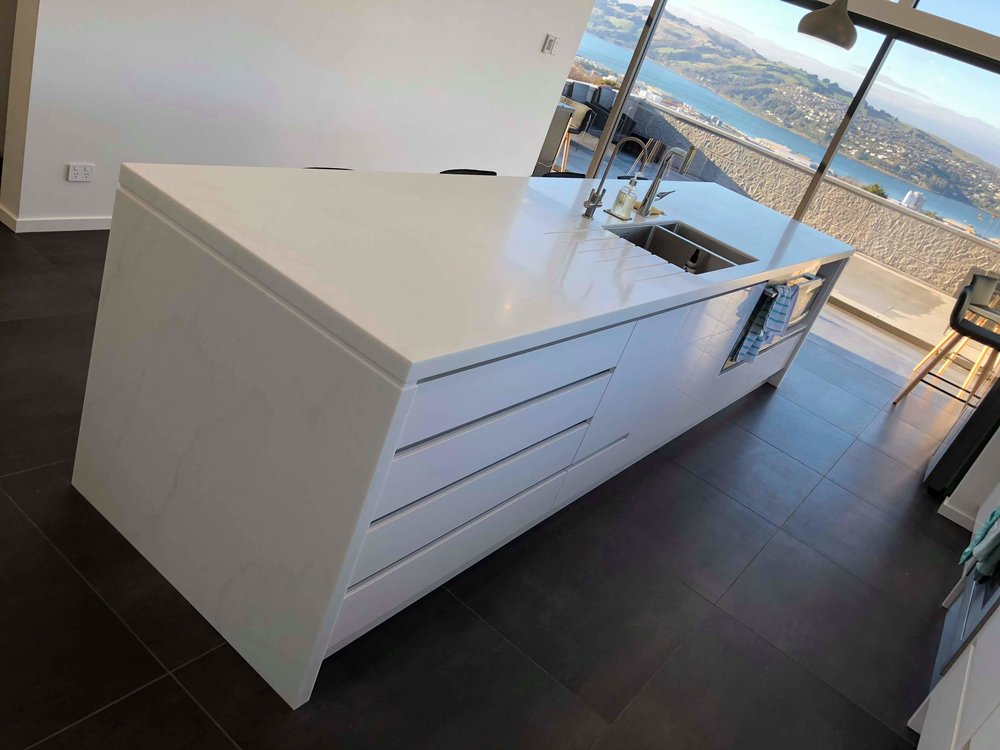 Kitchen island and back bench in Staron White Cotton.  Island features two negative detailed waterfall ends, undermounted sink, and drainer grooves.