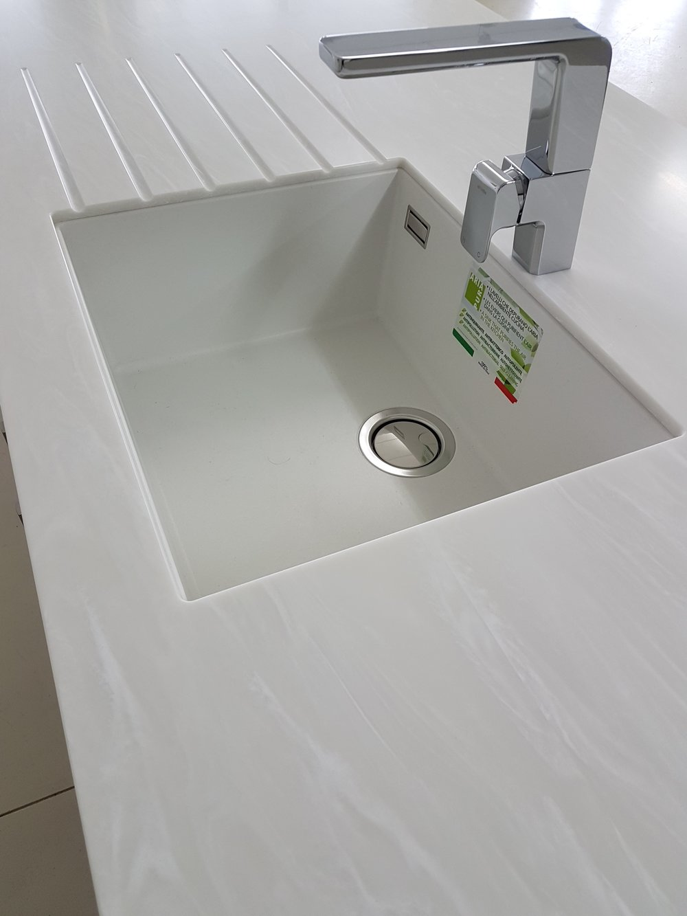 TriStone Milk Grotto benchtop with drainer grooves and undermounted white composite sink.