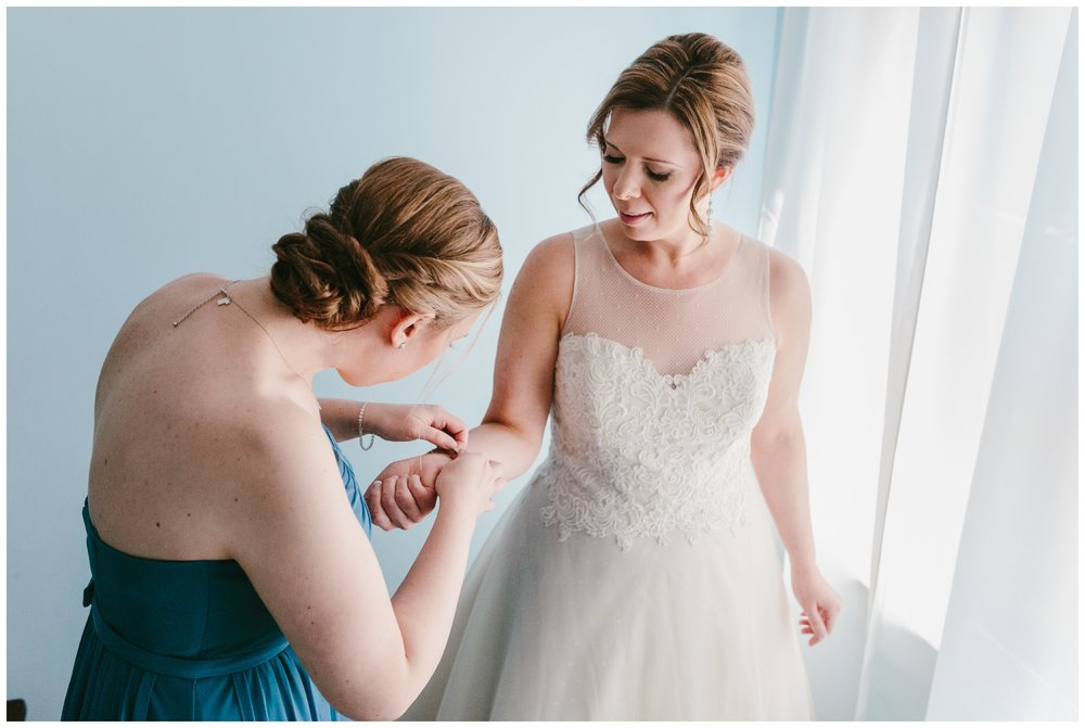 the bride's sister helps her put on her bracelet which was gifted to her by her groom