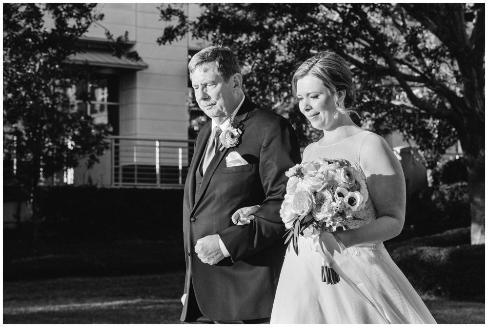 bride being walked down the isle by her father on the lawn of harborside east in mt. pleasant.