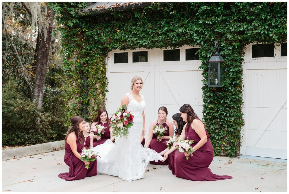 the bridesmaids help fluff the gown in front of the garage at old wide awake park.