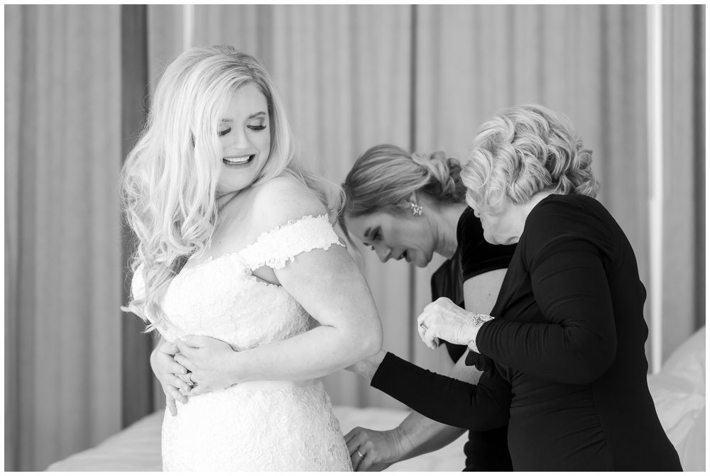 mother and sister helping bride get into her gown