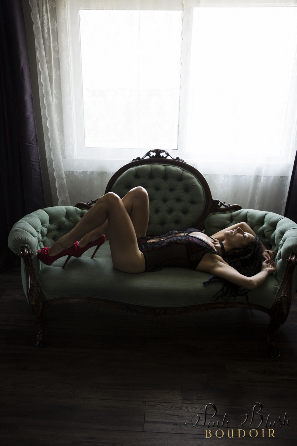 Boudoir Photography Edmonton, woman arched on a couch in a black and red lace bodysuit
