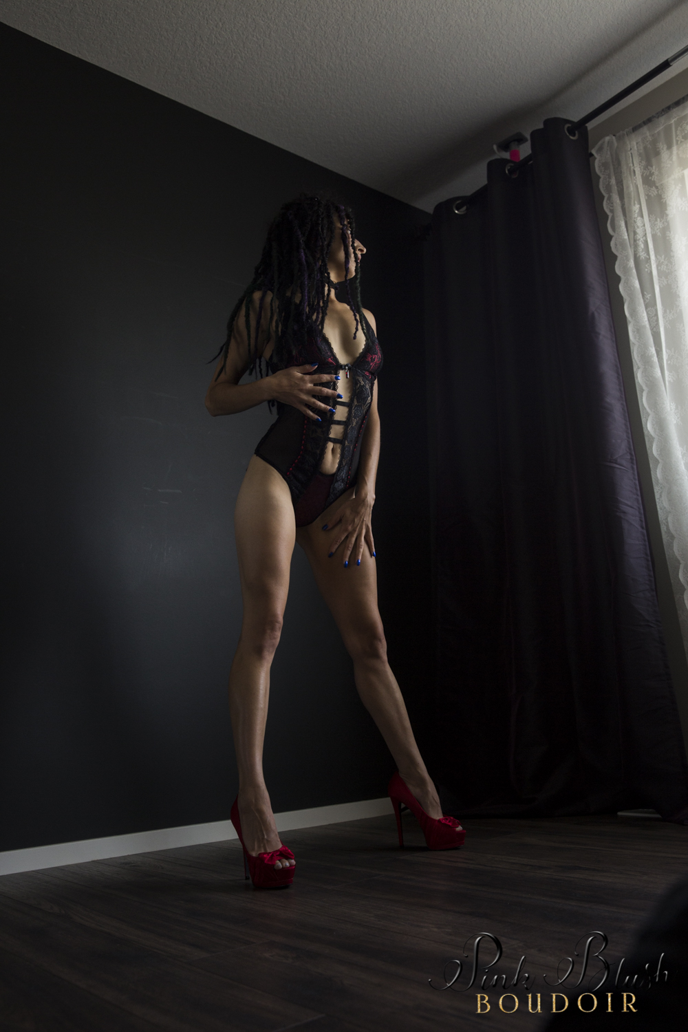 Boudoir Photography Edmonton, woman standing in a black and red lace body suit