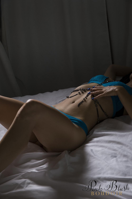 Boudoir Photography Edmonton, woman laying on her back dramatic lighting