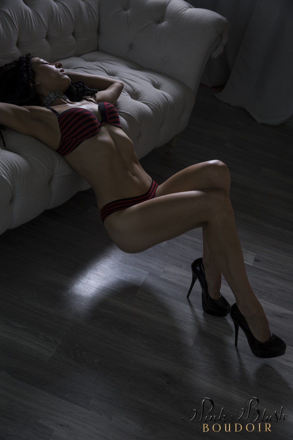 Boudoir Photography Edmonton, woman arched over a couch in a black and red bra and panty set