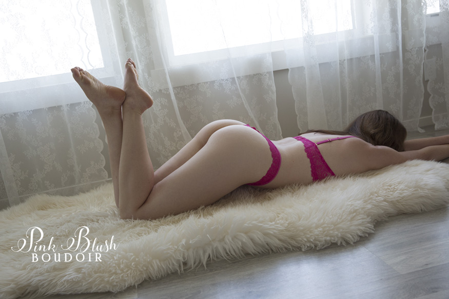 Edmonton Boudoir, a woman laying on her stomach wearing a hot pink bra and panty set