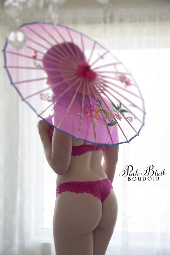 Edmonton Boudoir, a woman standing in front of a window holding a pink parasol