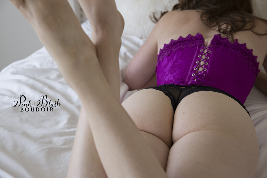 Edmonton Boudoir, a woman's butt laying on a white bed in a purple corset