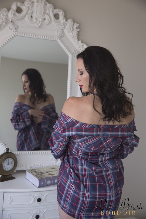 Boudoir Photos, a woman standing in front of a white mirror wearing a plaid shirt