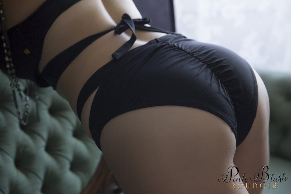Boudoir Photography, a woman wearing black panties leaning over a green couch