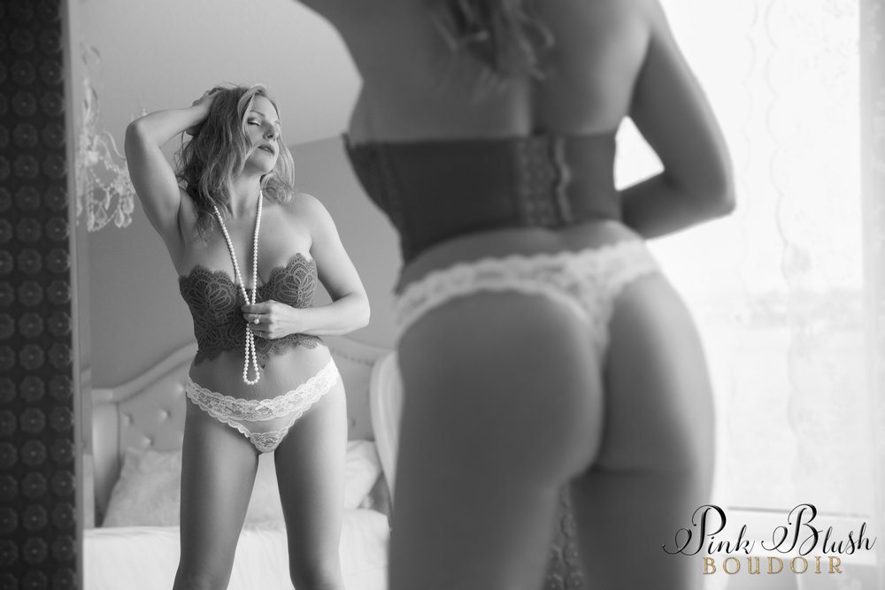 boudoir photos, a woman standing in front of a mirror, her butt is in the foreground