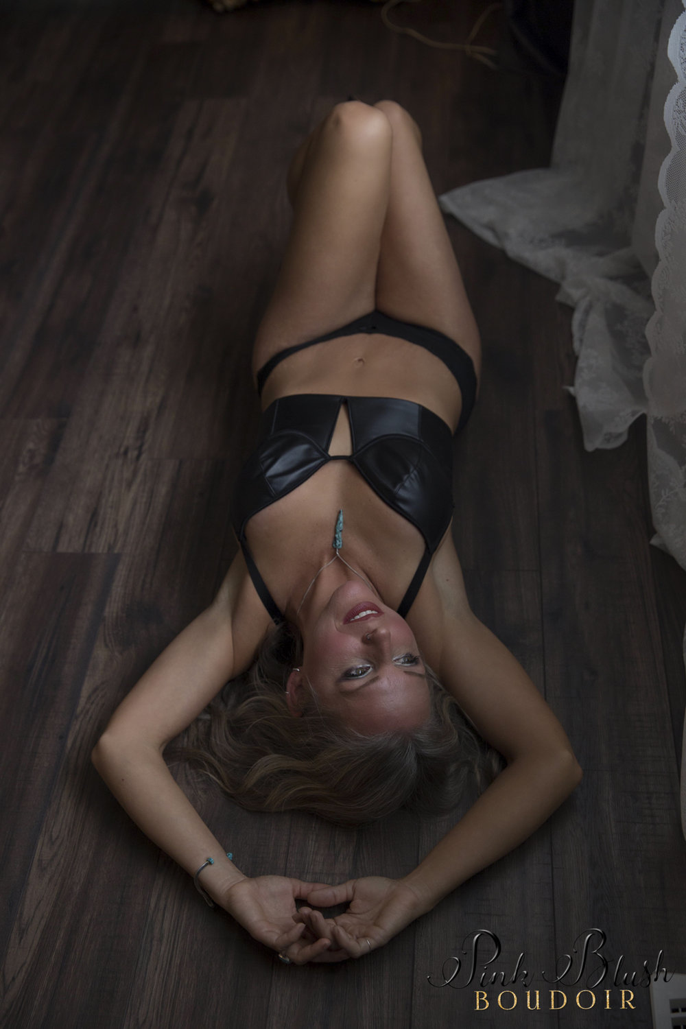 boudoir photos, a woman in a black bra and panty set laying on a hardwood floor