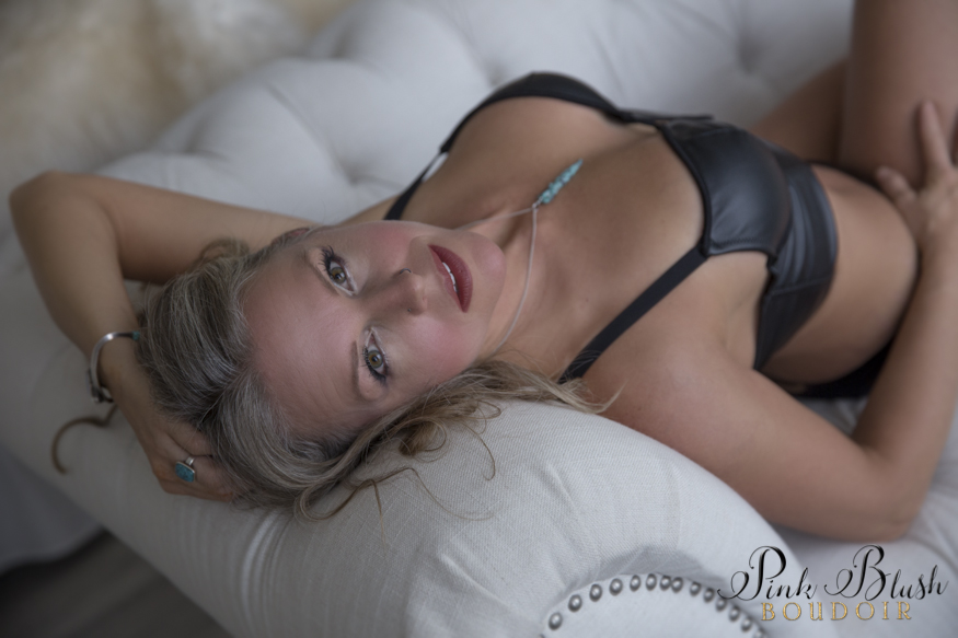 boudoir photos a woman in a black bra and panty set on a white couch
