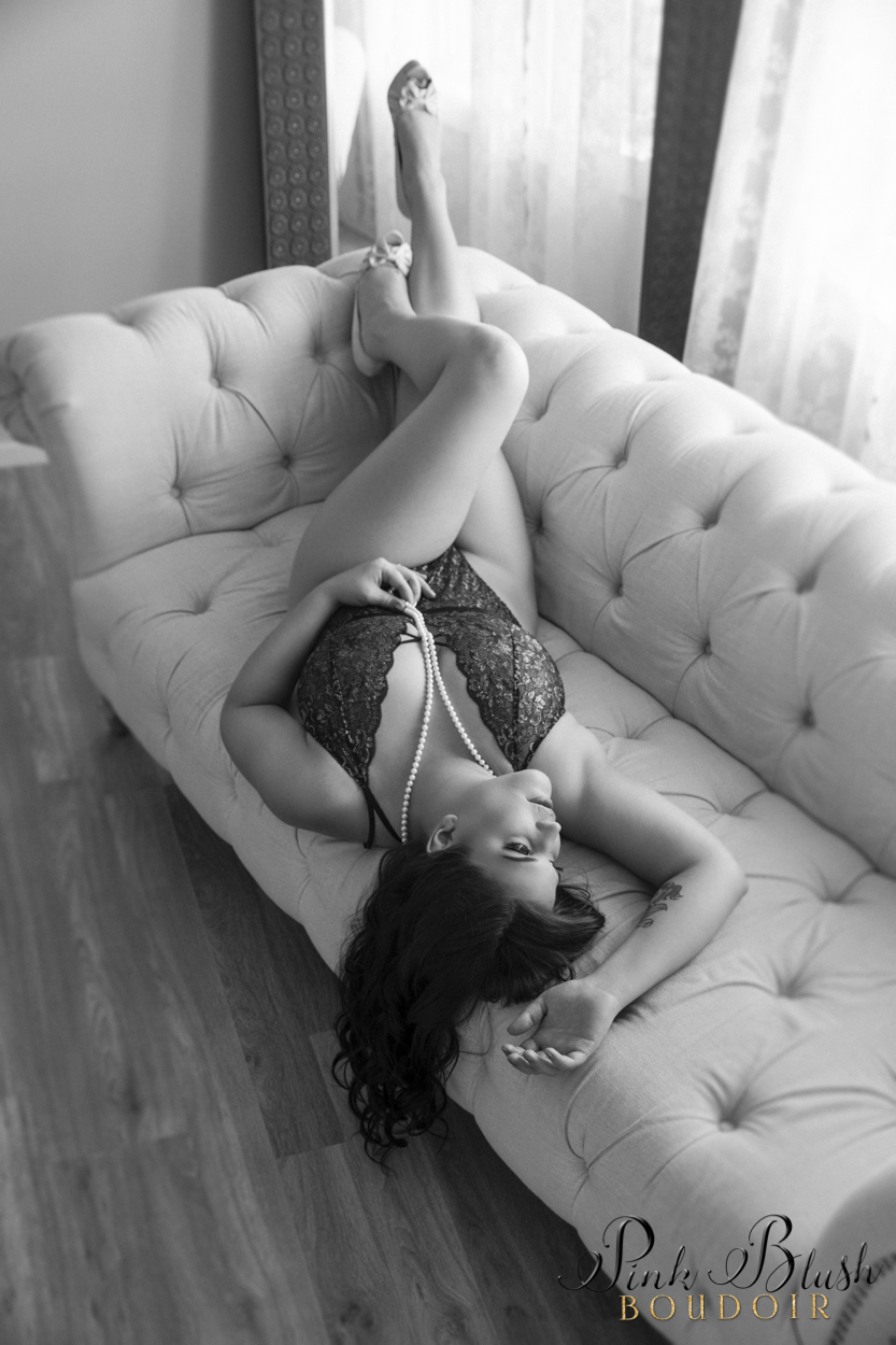 boudoir photography, a curvy woman in a lace teddy on a white couch