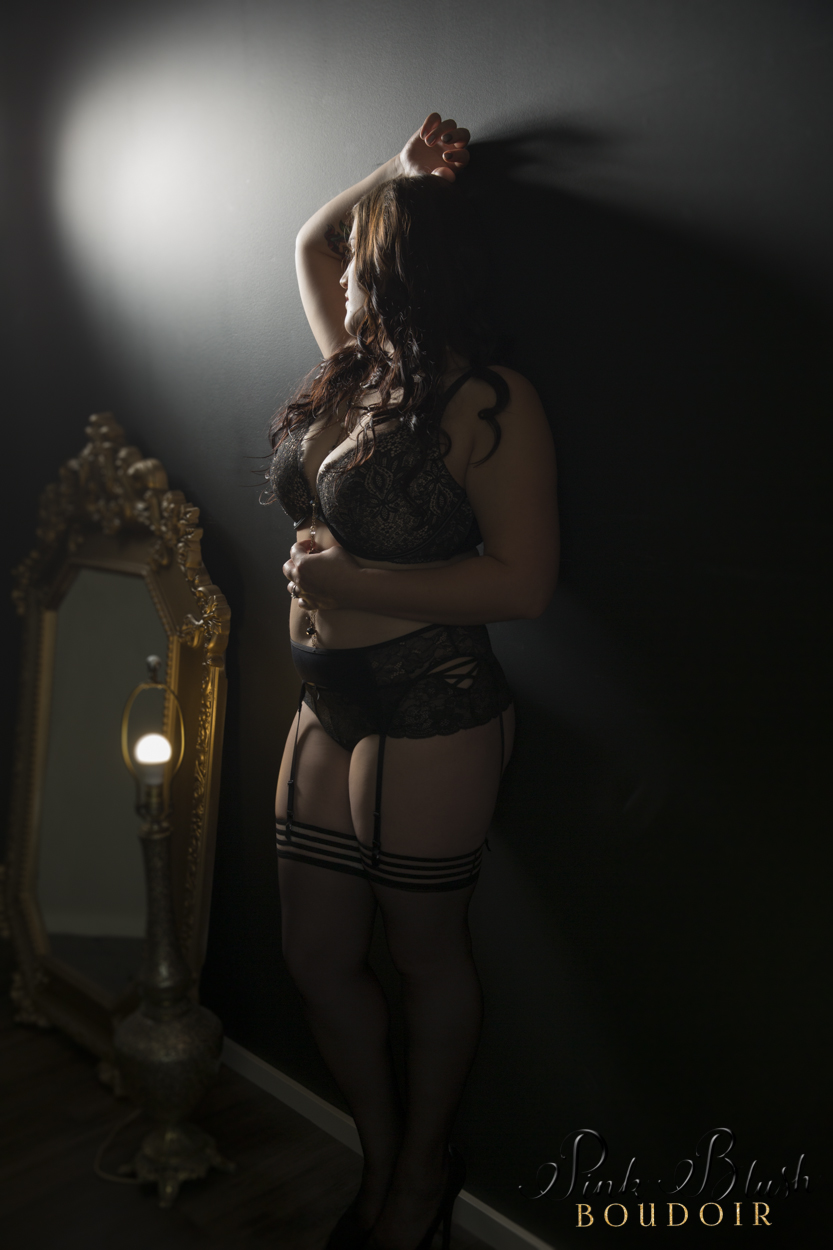 boudoir photography, a curvy woman standing against a black wall