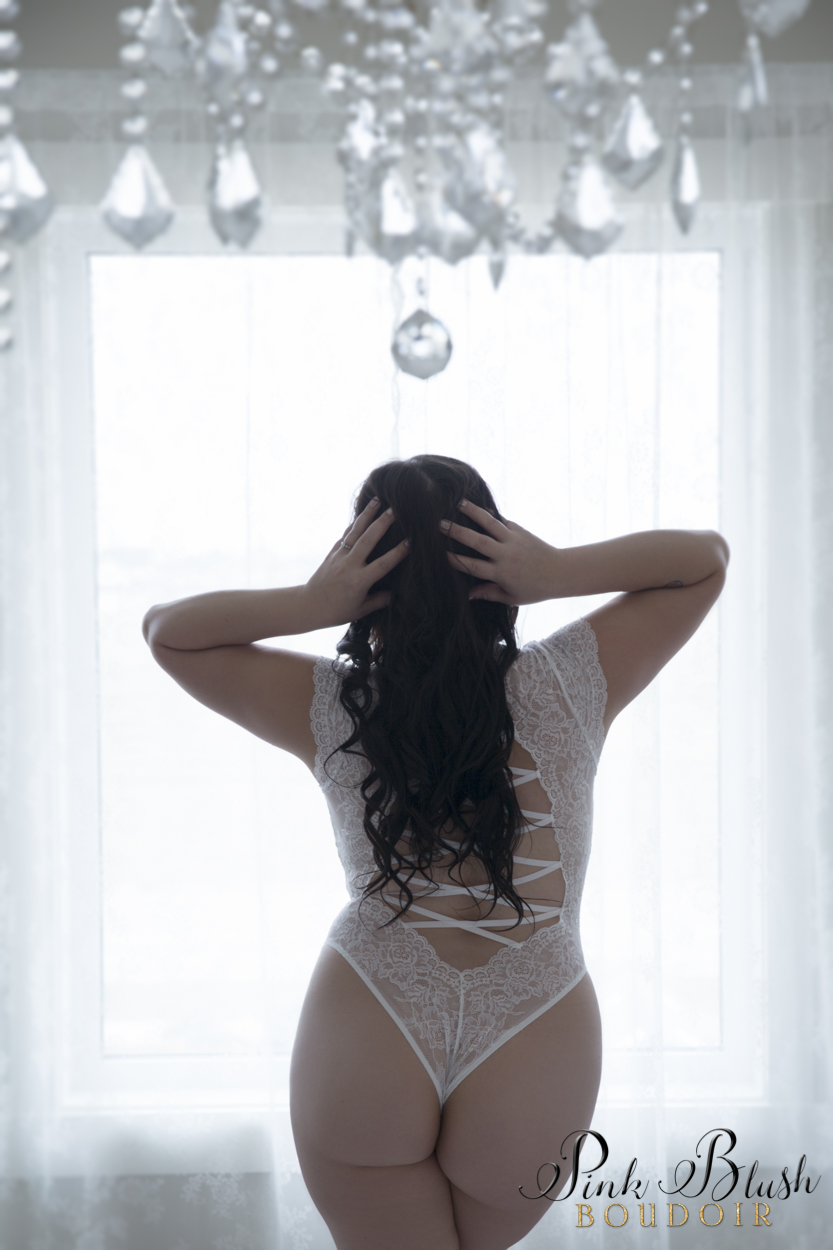 boudoir photography, a curvy woman in a white bodysuit standing in front of a window
