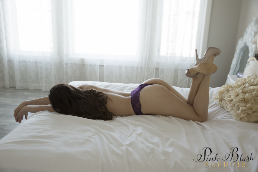 Boudoir Photos EdmontonA topless woman wearing purple panties laying on a white bed.
