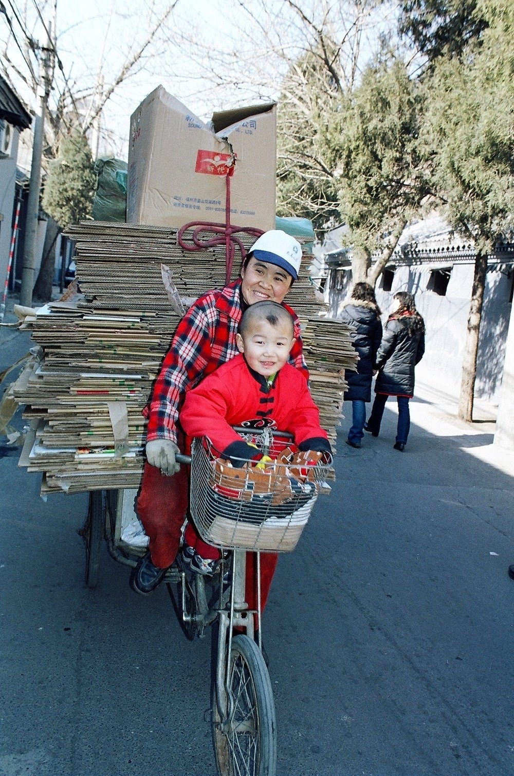 Mom and little boy with cardboard on bike.JPG
