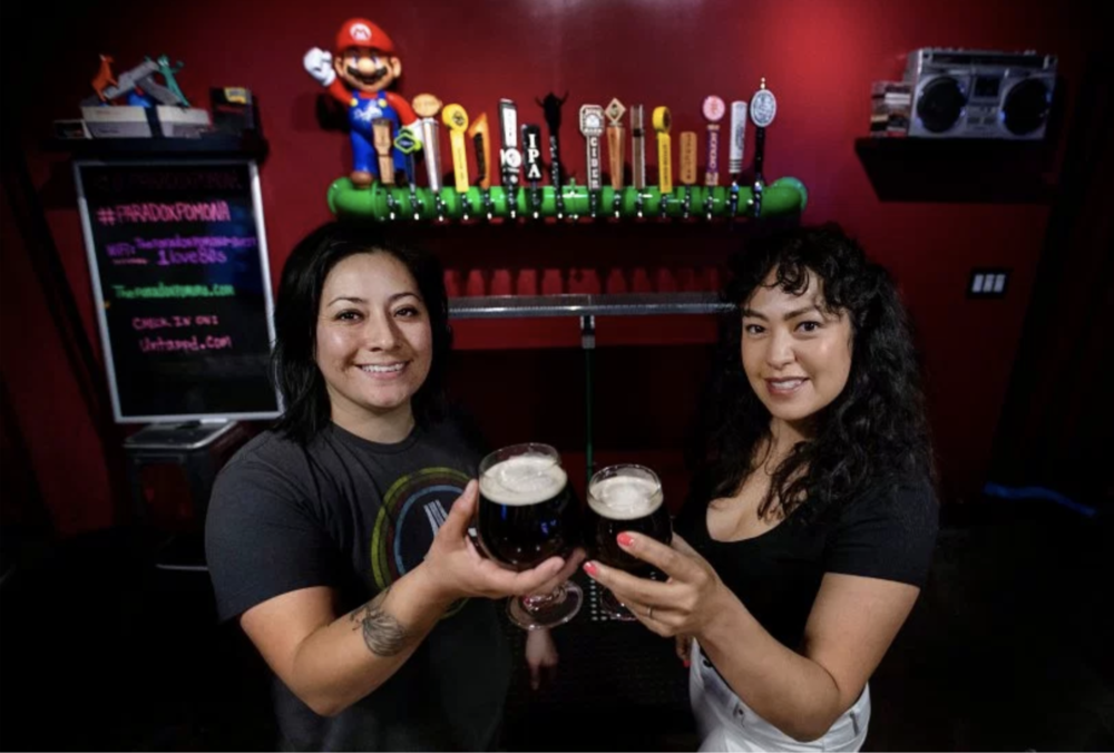 Owners and married couple Evelina Gamboa and Sabrina Gamboa of Pomona own The Paradox Arcade+Bar which features pinball machines, upright arcades as well as console games tap beer and some wines in Pomona on Thursday, January 31, 2019. (Photo by Terry Pierson, The Press-Enterprise/SCNG)