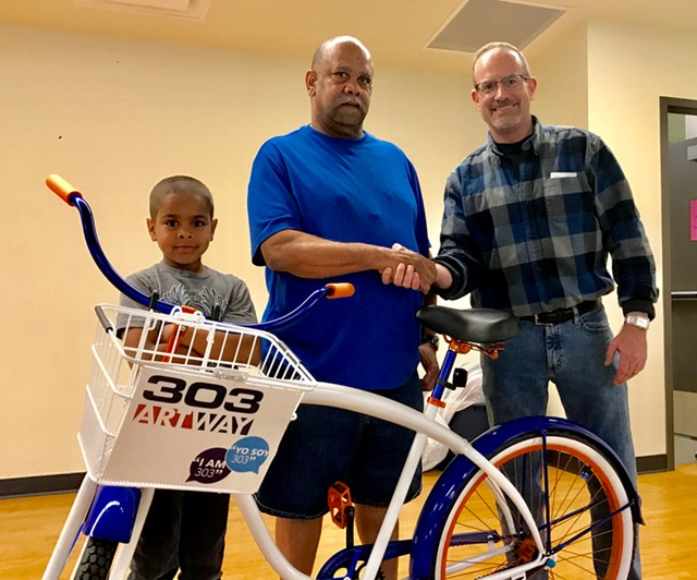 Will Kralovec, Director of Master Site Development at the ULC, and organizer of the 303 ArtWay Bike Giveaway Events, congratulates Eric Johnson on winning the free bike.
