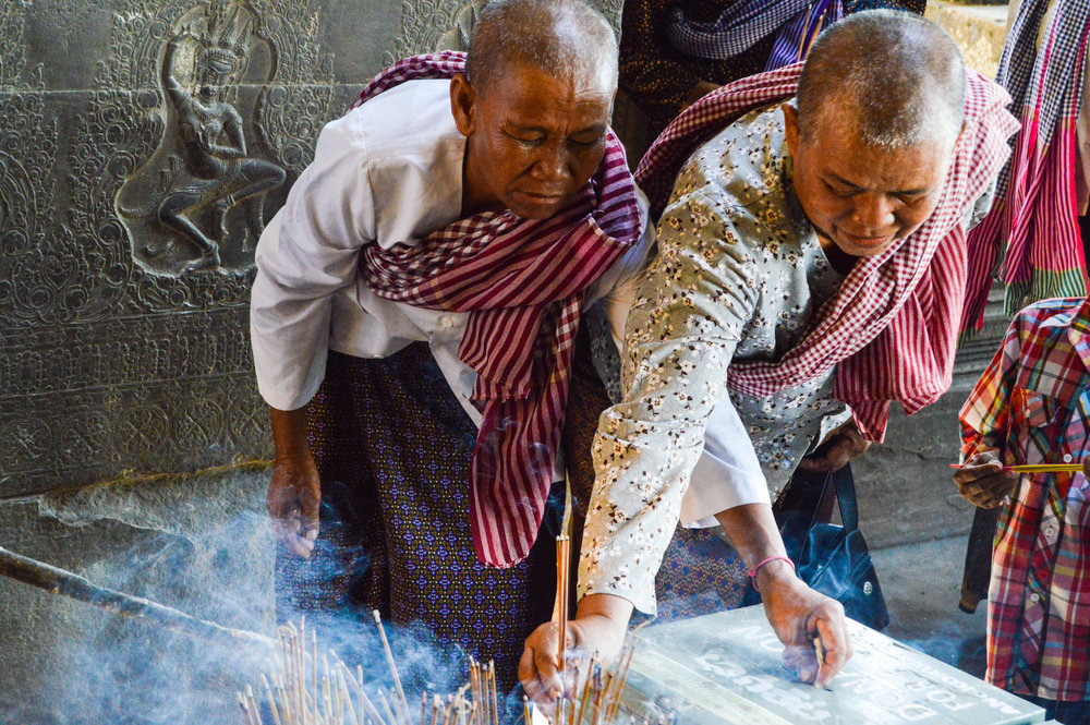 Nuns in Cambodia lighting incense