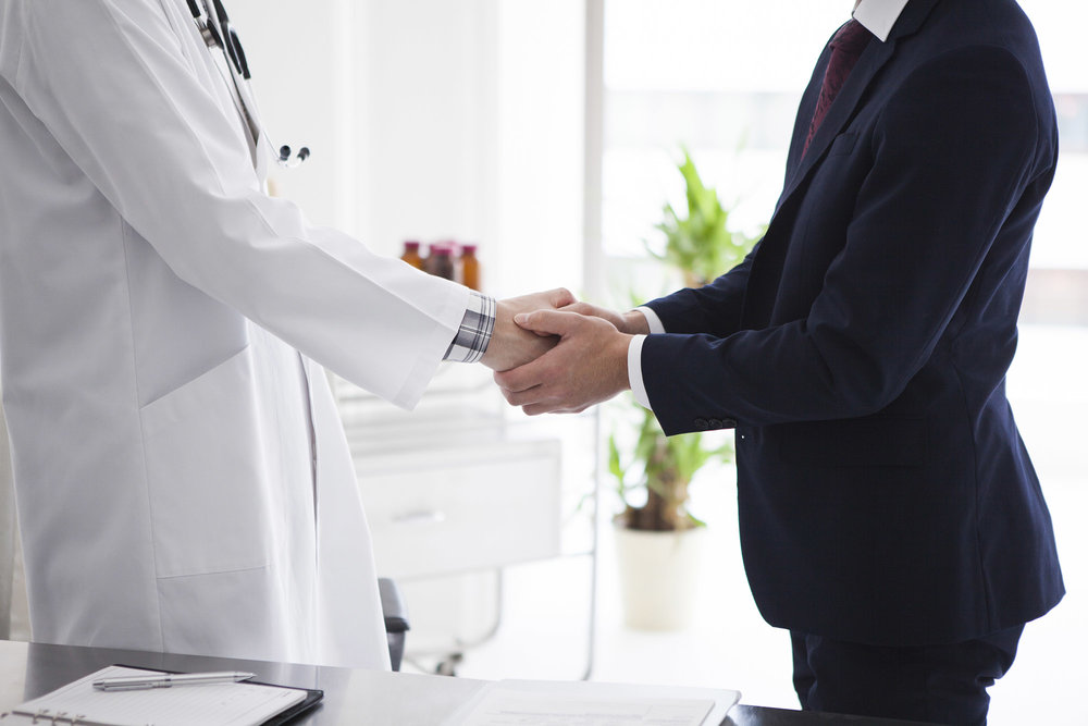 Doctor and businessman are shaking hands