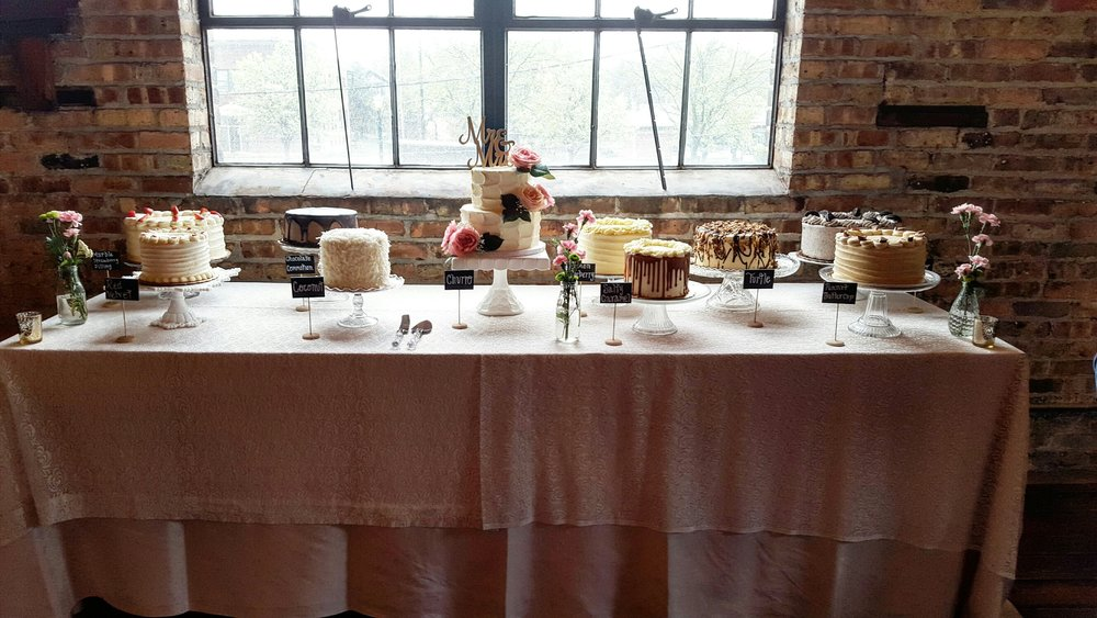 This Sweets Table includes a small tiered cake for the bridal couple's cutting cake, and layered cakes in the following flavors:  Red Velvet, Vanilla Strawberry, Chocolate Commotion, Coconut, Lemon Drop, Salty Caramel, Turtle, Oreo and Peanut Butter Cup