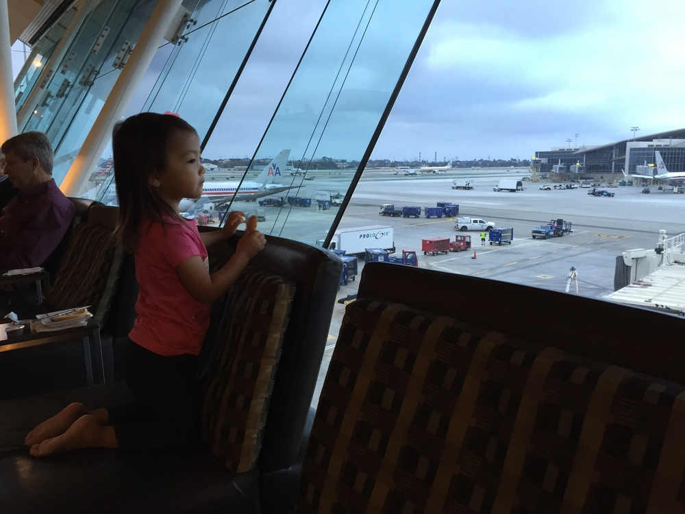 My daughter enjoying watching the planes from the American Airlines Admiral Lounge, prior to our flight to Turks & Caicos!
