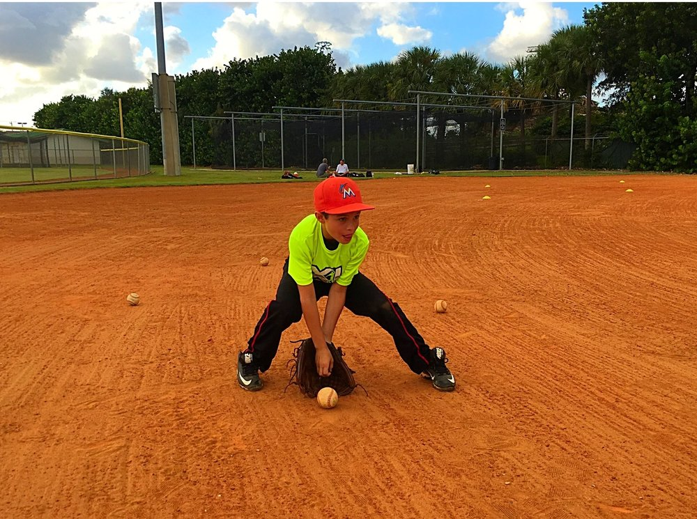 local 9u ball player going through proper fielding drill
