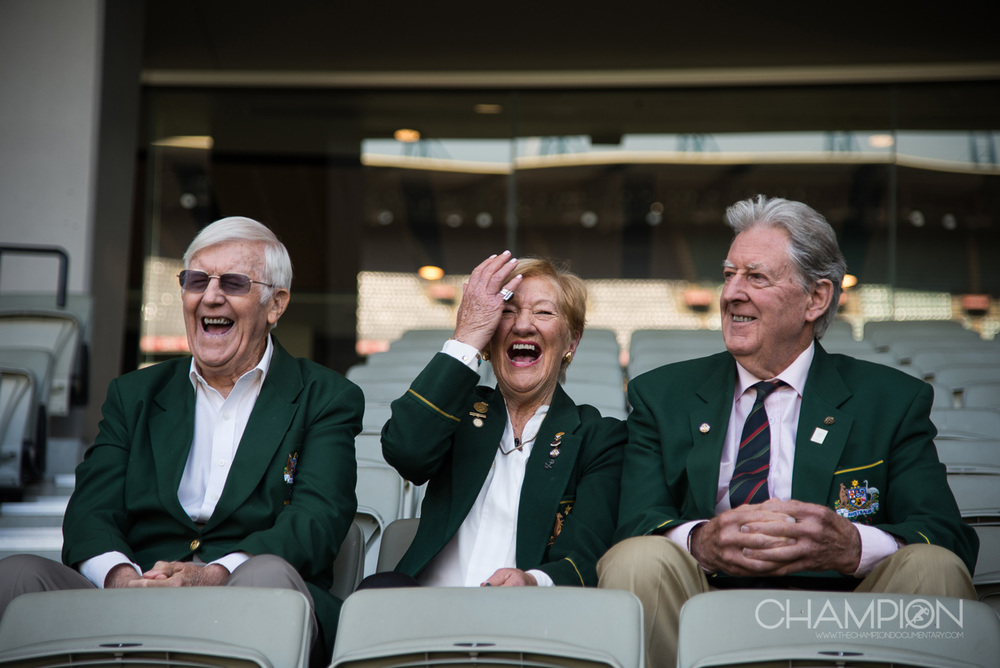CHAMPION – 1956 Olympians, Neil Robbins, Marg Woodlock-McLean and Bob Joyce at the MCG, Melbourne during filming