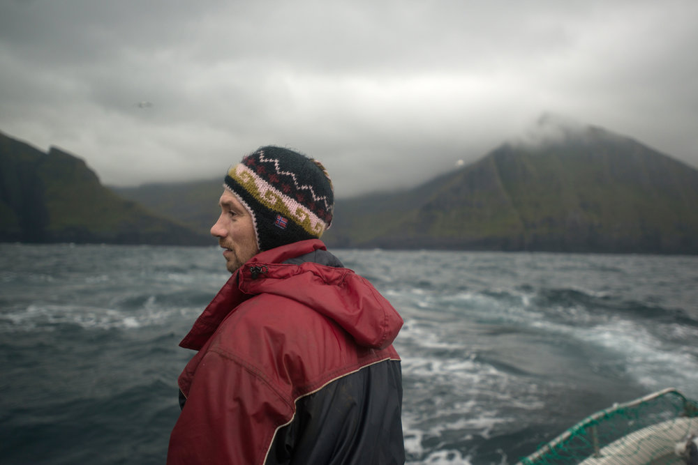 Bárður Isaksen, a fisherman, scans the sea for seabirds to catch for the table. He will provide his family with fulmars, guillemots, shags, and other local birds, but he is always hopeful tospot a pod of pilot whales.