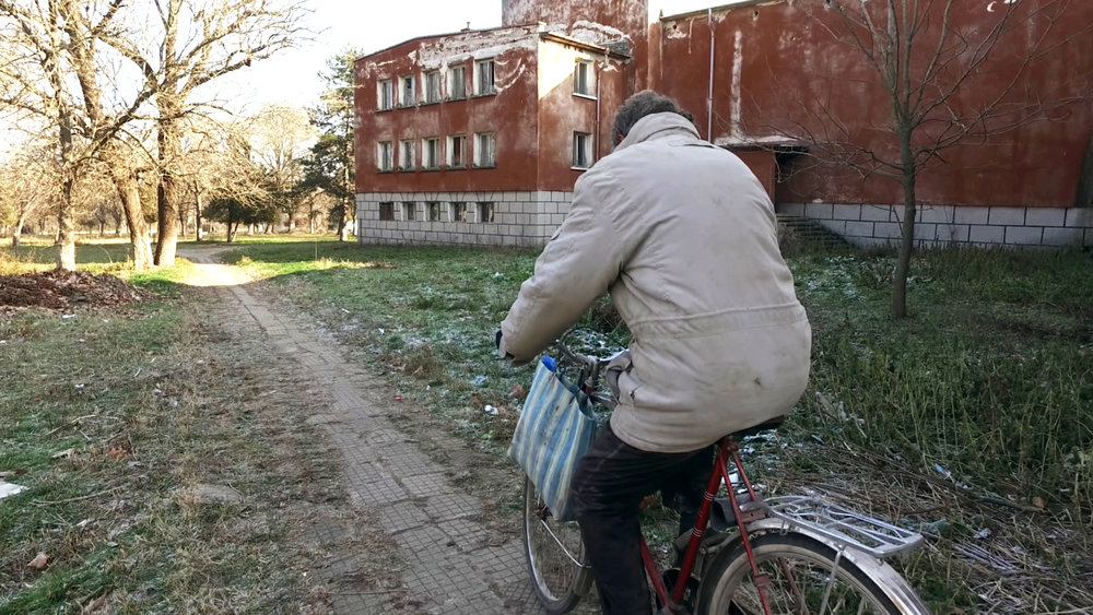 Altimir - Yordan ride his bike by the crumbling Cultural House, once a strong symbol of the communist ideology.