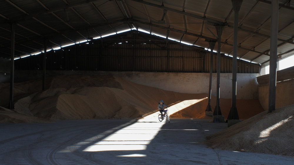 Altimir - Gosho rides his bike through the empty factory that used to employ hundreds of people.