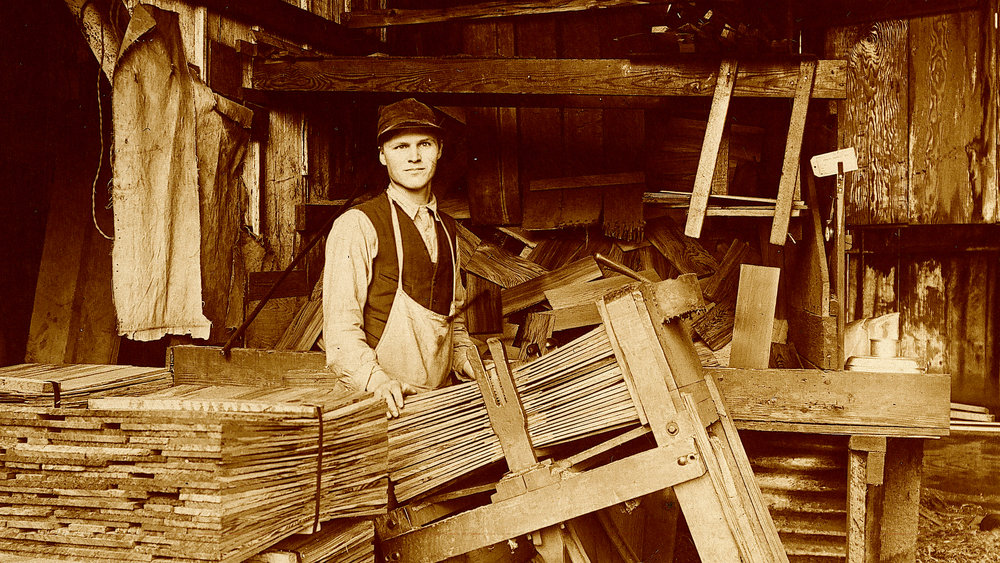 "Single man in mill: Shingle packer at the Union Mill, 1910. Shingle packers worked so fast, it appeared they were weaving shingles together. This earned them the name, ""shingle weavers,"" a name that soon applied to everyone who worked in a shingle mill. Courtesy of the Northwest Room, Everett Public Library."