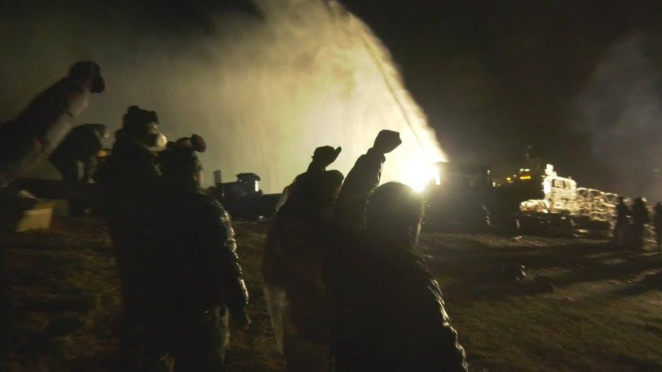 On November 20th militarized police fired water cannons, tear gas, and concussion grenades at Water Protectors during freezing temperatures. Image from AWAKE, A DREAM FROM STANDING ROCK captured by James Spione