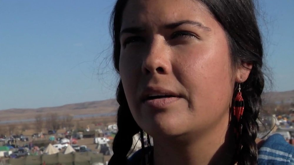 Tara Zhaabowekwe Houska at Oceti Sakowin Camp. Image from the film AWAKE, A DREAM FROM STANDING ROCK captured by Josh Fox.