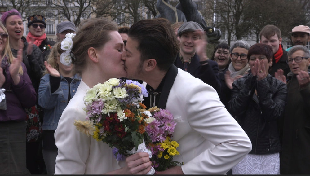 I Am They - Fox and Owl kissing at their protest wedding.