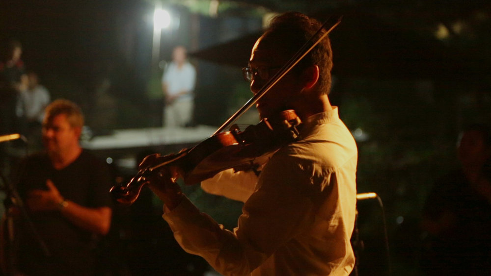 Hyungjoon Won warms up his violin at night at a border village. Photographer: Chapin Hall