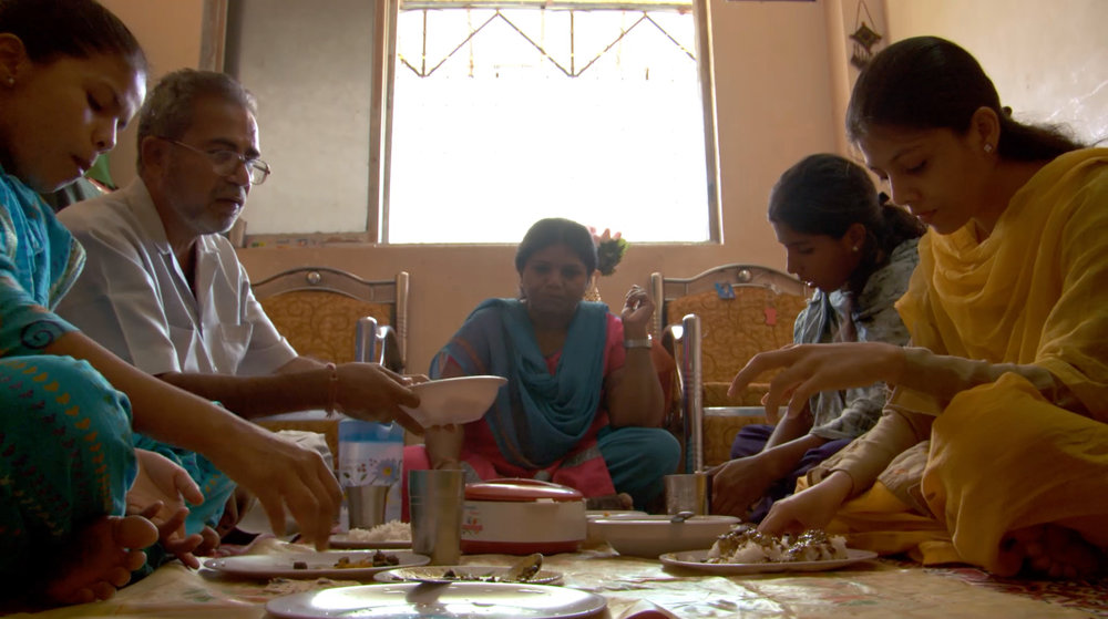 The Mirza family eating dinner at their home in Mumbai. From the feature documentary, Purdah. Dir. Jeremy Guy. Image courtesy of Jeremy Guy Films, LLC.
