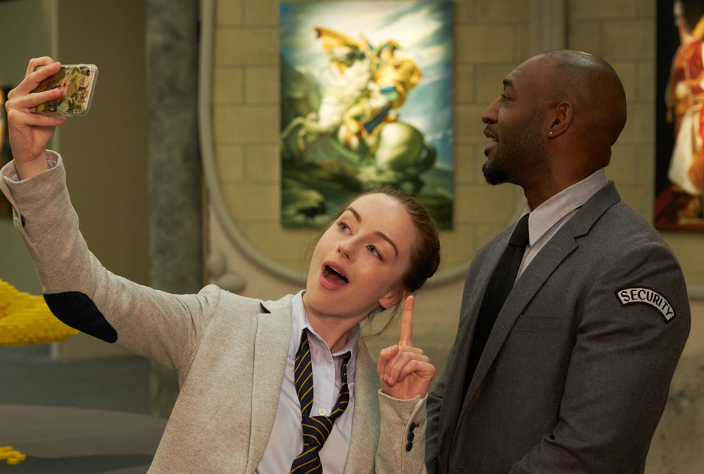 """Kacey Rohl as the """"Selfie Girl"""" and Adrian Holmes as the """"Security Guard"""""""
