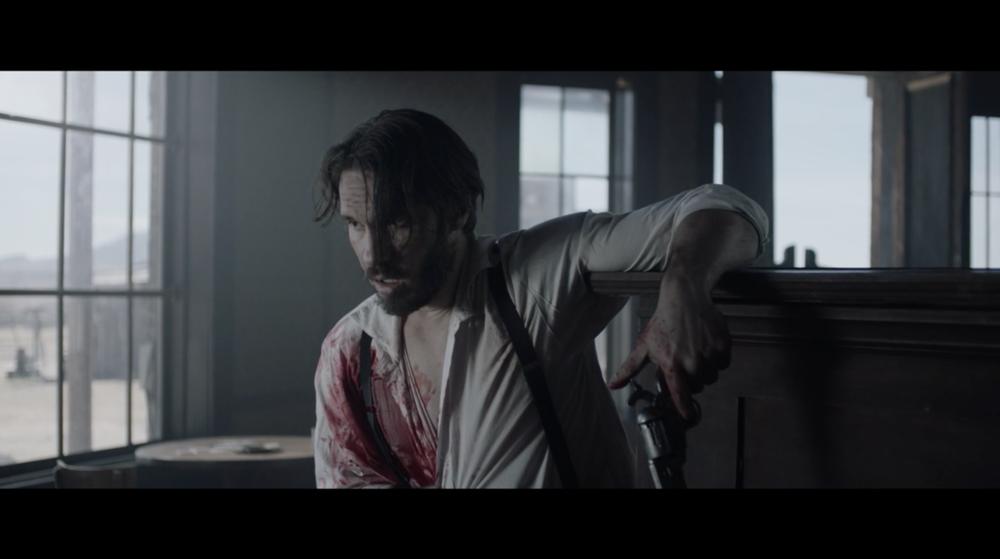 """""""Blake"""" (Jordan Jones) bleeds over a broken piano after a shoot out with """"Sara"""" (Naiia Lajoie)."""