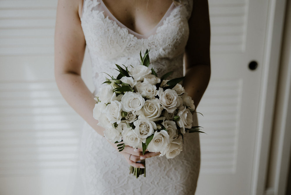 lace wedding dress and ivory rose bouquet