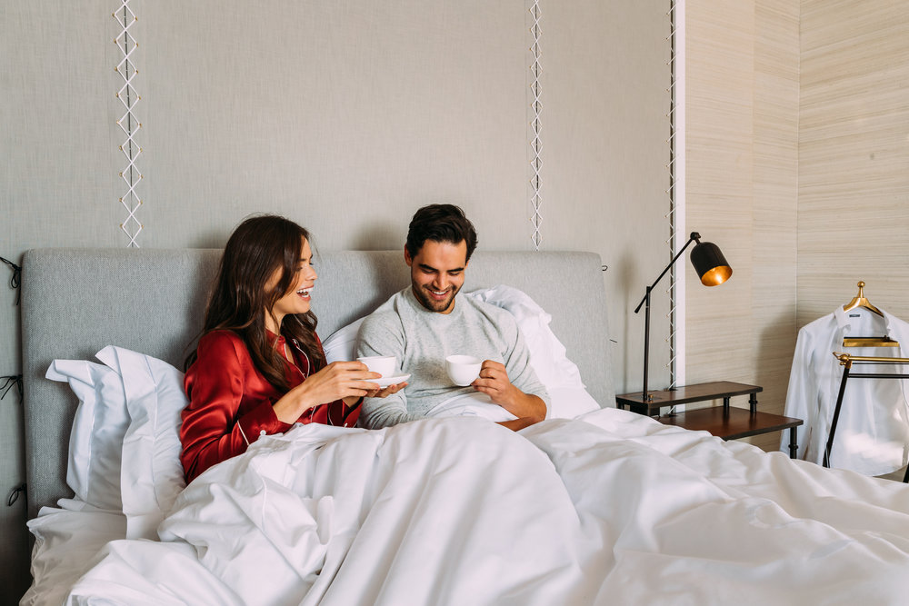 A couple having coffee in bed in the Presidential Lodge at Delaire Graff Lodges & Spa