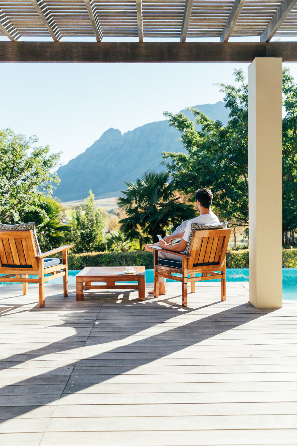 A man sitting on the private deck of the Presidential Lodge enjoying the views across the Stellenbosch Valley from Delaire Graff Lodges & Spa
