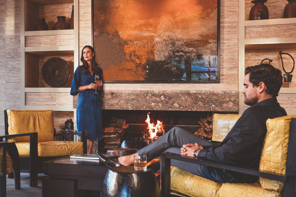 An elegant couple enjoy pre-dinner drinks by the fire at Delaire Graff Lodges & Spa reception