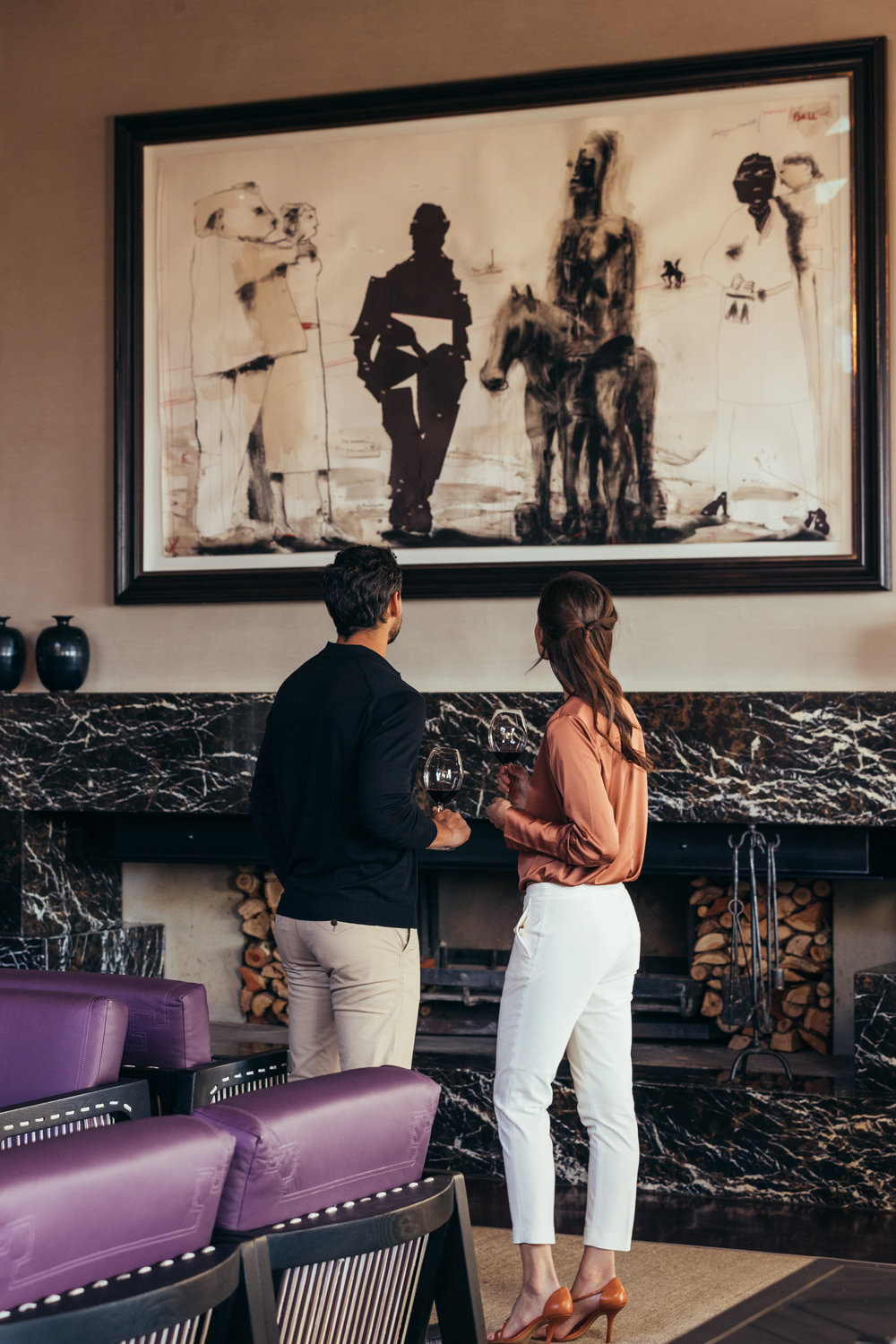 A couple stand by the fireplace and admire an artwork from Laurence Graff's private collection at the Wine Lounge at Delaire Graff Estate